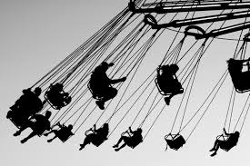 swinging people on ride black and white